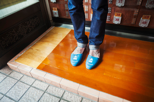A man in jeans, with his bare feet in rubber slippers.の写真素材 [FYI02261044]