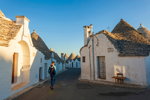 Man walking down Mediterranean street lined with traditional white washed round stone houses with coの写真素材 [FYI02261057]