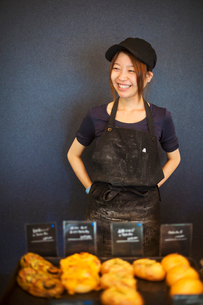 Smiling woman wearing baseball cap and apron standing in a bakery, trays with freshly baked goods.の写真素材 [FYI02261073]