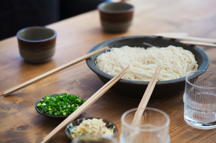 High angle close up of bowl with noodles and pairs of wooden chopsticks on a table.の写真素材 [FYI02261076]