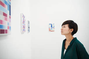 Woman with short black hair wearing green shirt standing in art gallery, looking at modern painting.の写真素材 [FYI02261090]