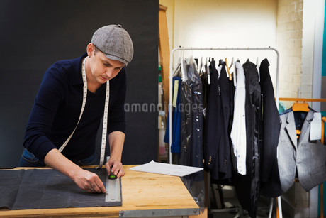 A man at a workbench measuring and marking a piece of grey fabric with tailor's chalk.の写真素材 [FYI02261091]