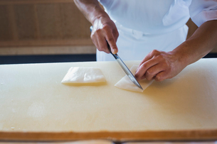 High angle close up of chef working at a counter at a Japanese sushi restaurant, slicing squid.の写真素材 [FYI02261097]