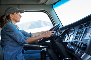 Caucasian woman truck driver in the cab of her commercial truck at a truck stopの写真素材 [FYI02261101]
