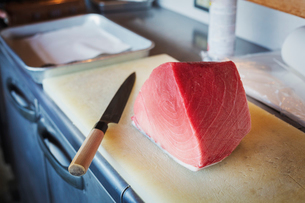 High angle close up of a fillet of tuna on chopping board  on counter at Japanese sushi restaurant.の写真素材 [FYI02261102]