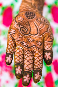 High angle close up of female hand covered in Henna tattoos with intricate geometric, floral and folの写真素材 [FYI02261106]