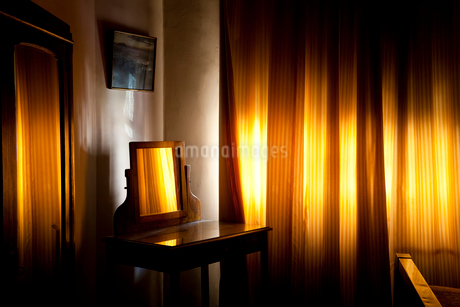 Room interior with vintage wooden dressing table with mirror, yellow light filtering through drawn cの写真素材 [FYI02261111]