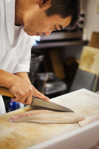 Chef working at a counter at a Japanese sushi restaurant, slicing fillet of fish.の写真素材 [FYI02261113]
