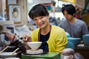 Smiling woman and man sitting in a workshop, working on Japanese porcelain bowls.の写真素材 [FYI02261117]