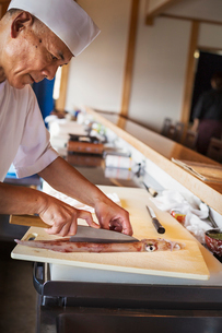 Chef working at a counter at a Japanese sushi restaurant, cutting a squid.の写真素材 [FYI02261121]