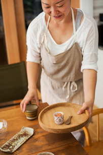 Smiling woman wearing apron holding small round wooden tray with bowl of crushed ginger and spoon, pの写真素材 [FYI02261127]