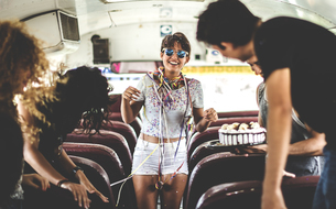 A young woman having a birthday party on a bus.の写真素材 [FYI02261131]