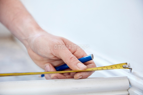 A man using a steel measuring tape, to measure, holding a small pencil.の写真素材 [FYI02261136]