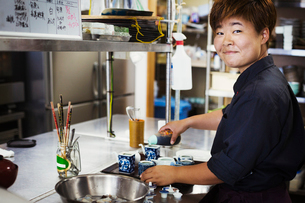 Waitress working in the kitchen of a Japanese sushi restaurant, smiling at camera.の写真素材 [FYI02261146]