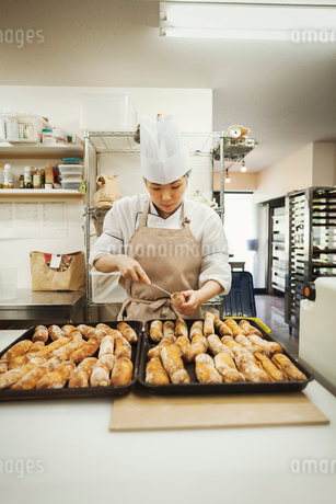 Woman wearing chef's hat and apron working in a bakery, preparing freshly baked rolls on large traysの写真素材 [FYI02261154]
