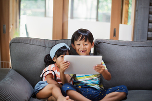 Boy and young girl with black hair sitting on a grey sofa, looking at digital tablet.の写真素材 [FYI02261158]