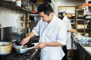 Chef working in the kitchen of a Japanese sushi restaurant, cooking on stove.の写真素材 [FYI02261173]