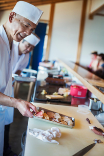 Two chefs working at a counter at a Japanese sushi restaurant, holding metal tray with fresh fish anの写真素材 [FYI02261179]