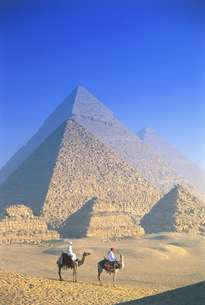 Two people on camels in front of Egyptian pyramids.の写真素材 [FYI02261180]