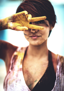 Young woman holding two paint-stained fingers in front of her face, looking at camera. Paint coveredの写真素材 [FYI02261181]