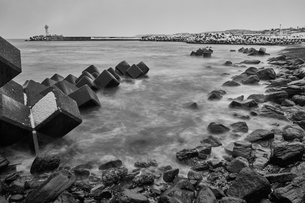 Snow-covered wave breakers on a rocky beach in winter.の写真素材 [FYI02261183]