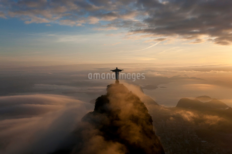 High angle view of colossal Christ Redeemer statue surrounded by clouds at dusk, Corcovado, Rio de Jの写真素材 [FYI02261185]