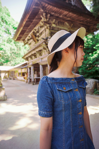 Young woman wearing blue dress and hat standing at Shinto Sakurai Shrine, Fukuoka, Japan.の写真素材 [FYI02261188]