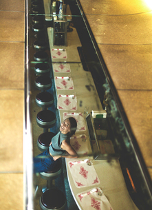 High angle view of woman sitting at a bar counter looking up at the camera, smiling.の写真素材 [FYI02261193]