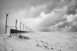 Snow-covered winter landscape under a cloudy sky with a row of wind turbines.の写真素材 [FYI02261208]
