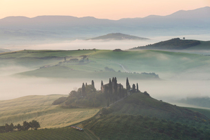 Sunrise across a misty Italian landscape of rolling hills and cypress trees, farmhouse in the distanの写真素材 [FYI02261217]