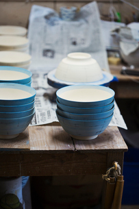 Close up white bowls with  blue glaze in a Japanese porcelain workshop.の写真素材 [FYI02261220]