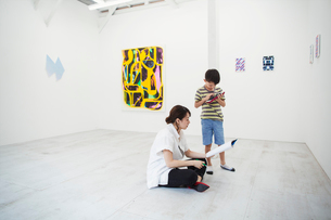 Woman with black hair wearing white shirt sitting on floor in art gallery with pen and paper, boy stの写真素材 [FYI02261221]