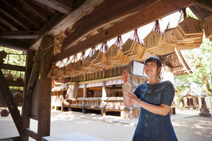 Young woman wearing blue dress looking at wooden fortune telling plaques at Shinto Sakurai Shrine, Fの写真素材 [FYI02261227]