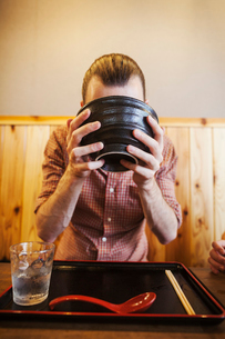 A western man in a noodle restaurant, with a noodle bowl lifting it with two hands to drink from it.の写真素材 [FYI02261230]