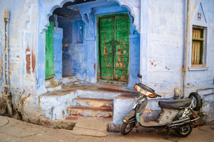 Motor scooter parked in front of traditional building entrance in Rajasthan, India.の写真素材 [FYI02261235]