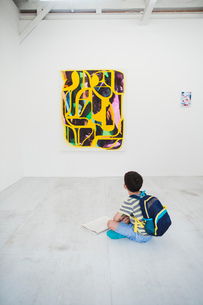 Boy with short black hair wearing backpack sitting on floor in art gallery with pen and paper, lookiの写真素材 [FYI02261244]