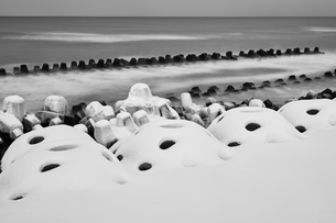 Snow-covered wave breakers on a rocky beach in winter.の写真素材 [FYI02261251]