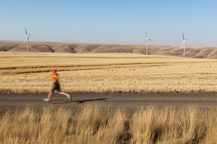 Man jogging on rural road, farmland and wind turbines in distance, Washingtonの写真素材 [FYI02261256]