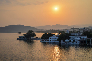 Sunset over a lake in Udaipur. Traditional historic buildings and an orange glow cast by the settingの写真素材 [FYI02261262]