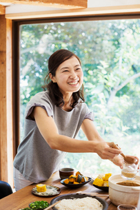 Smiling woman with black hair standing at a table with bowls of food, holding wooden ladle.の写真素材 [FYI02261265]