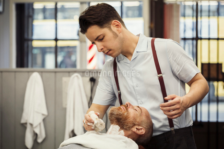 A customer sitting in the barber's chair, having a wet shave. A man using a shaving brush to latherの写真素材 [FYI02261266]