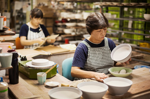 Two women sitting in a workshop, working on Japanese porcelain bowls.の写真素材 [FYI02261268]