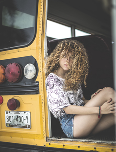 A young woman with long red curly hair sitting on the tailgate of a school bus.の写真素材 [FYI02261270]