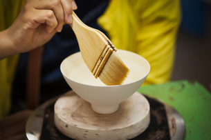 Close up of person working in a Japanese porcelain workshop, glazing white bowls with paintbrush.の写真素材 [FYI02261283]