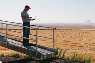 A wind farm technician standing and using a laptop at the base of a turbine on a wind farm in open cの写真素材 [FYI02261289]
