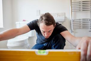 A builder using a spirit level to check his work, refurbushing a bathroom.の写真素材 [FYI02261298]