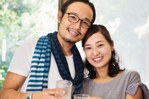 Portrait of smiling woman and man wearing glasses standing side by side, looking at camera.の写真素材 [FYI02261304]