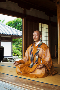 Buddhist monk with shaved head wearing golden robe sitting cross legged on the floor, meditating, Buの写真素材 [FYI02261307]