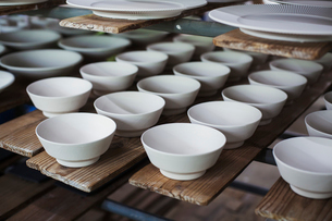 High angle close up of white bowls and plates in a Japanese porcelain workshop.の写真素材 [FYI02261330]