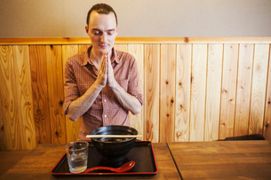 A western man in a noodle restaurant with his hands in prayer and eyes closed, saying a traditionalの写真素材 [FYI02261331]